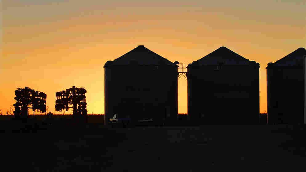 Farm equipment and grain silos are silhouetted against a setting sun near Farmingdale, Ill.