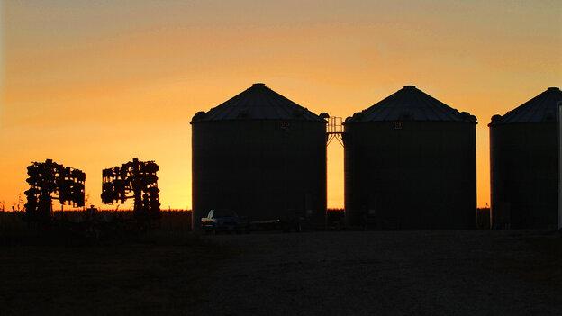 Farm equipment and grain silos are silhouetted against a setting sun near Farmingd