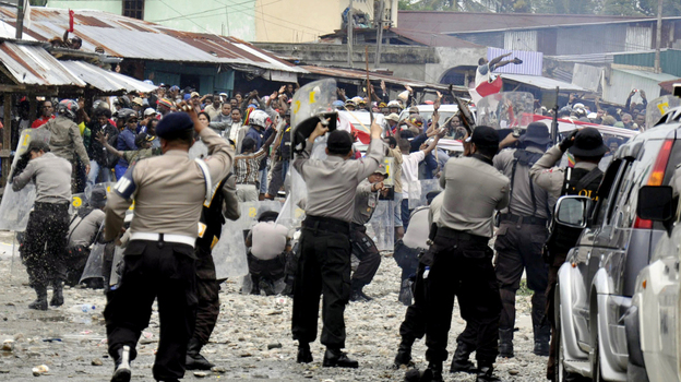 Police clash with workers of American mining company Freeport-McMoRan during a protest in Timika, Papua province, Indonesia, Oct. 10. Indonesian security forces fired on striking workers at Freeport-McMoRan's Grasberg gold and copper mine after a protest turned deadly. (AP)