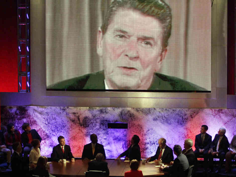 The eight Republican presidential candidates sitting at the table listen as a video of former President Ronald Reagan is played during a debate at Dartmouth College in Hanover, N.H., on Oct. 11.