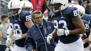Then-Penn State head coach Joe Paterno gets out of the way during warm-ups before an NCAA college football game in State College, Pa., last month.
