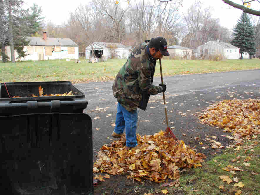 Detroit resident Kevin Garcia rakes leaves in front of his home. Abandoned homes are everywhere in his neighborhood.