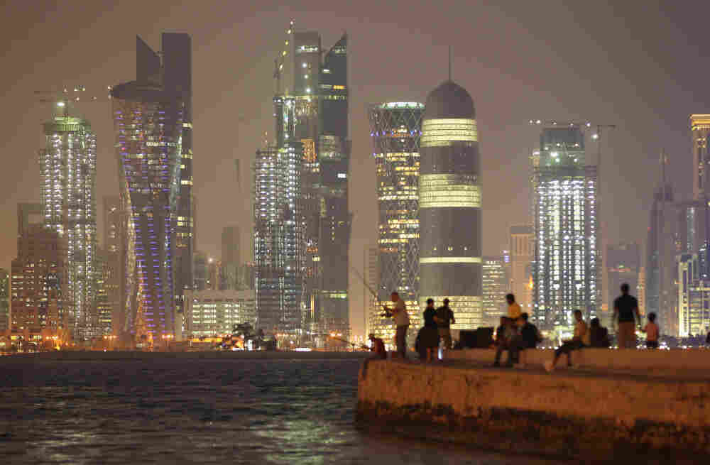 People fish at night across from skyscrapers in Doha, Qatar, in October 2011.