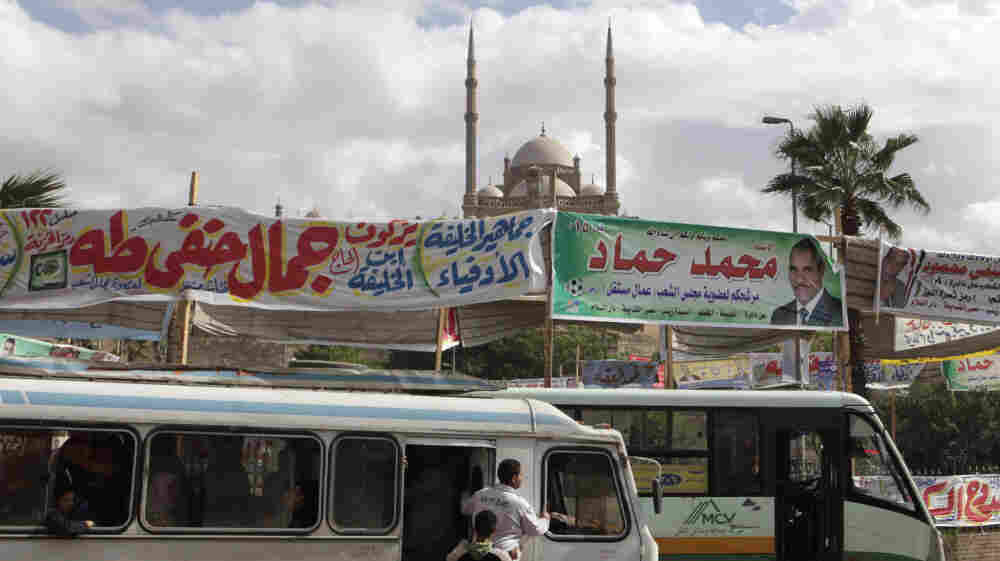 Election banners hang near buses in Cairo on Monday. Parliamentary elections — the first since the end of President Hosni Mubarak's decades-long rule — will begin Nov. 28. Groups with Islamist ties are expected do well in the polls.