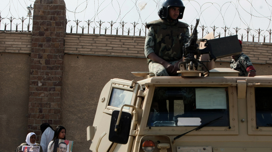 An Egyptian soldier stands guard as supporters of former President Hosni Mubarak gather outside the courts set up at the Police Academy in October.