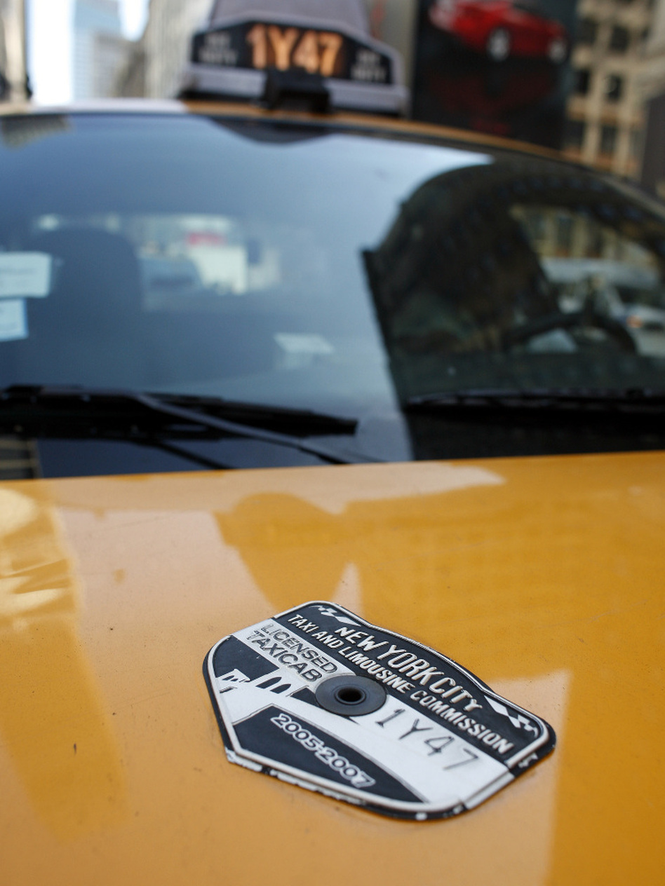 A New York City Taxi & Limousine Commission medallion adorns the hood of a taxi. The value of a medallion has increased 1,000 percent since 1980. (Chip East/Bloomberg via Getty Images)