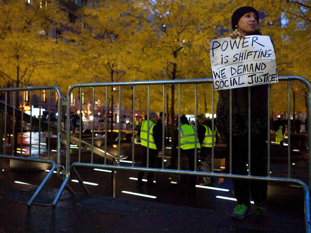 A solitary Occupy Wall Street protestor holds a sign outside a nearly empty Zuccotti Park, W
