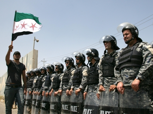Riot police stand guard as Syrian Kurds protest in front of the UN office in the northern Iraqi Kurdish city of Arbil, to demand the departure of the Syrian President Bashar al-Assad's regime, on June 27, 2011. (AFP/Getty Images)