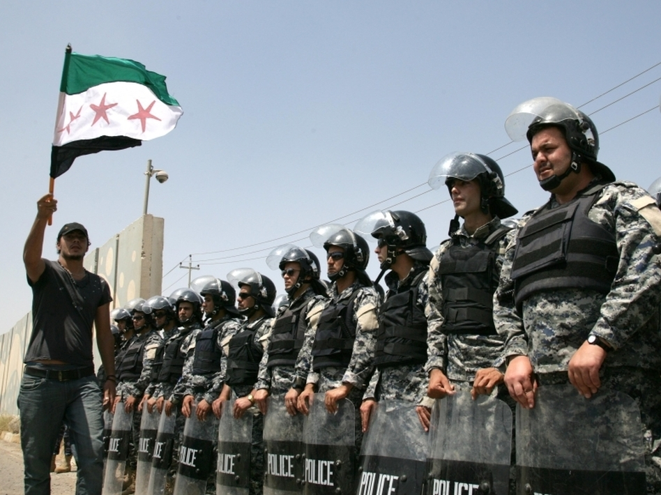 Riot police stand guard as Syrian Kurds protest in front of the UN office in the northern Iraqi Kurdish city of Arbil, to demand the departure of the Syrian President Bashar al-Assad's regime, on June 27, 2011.