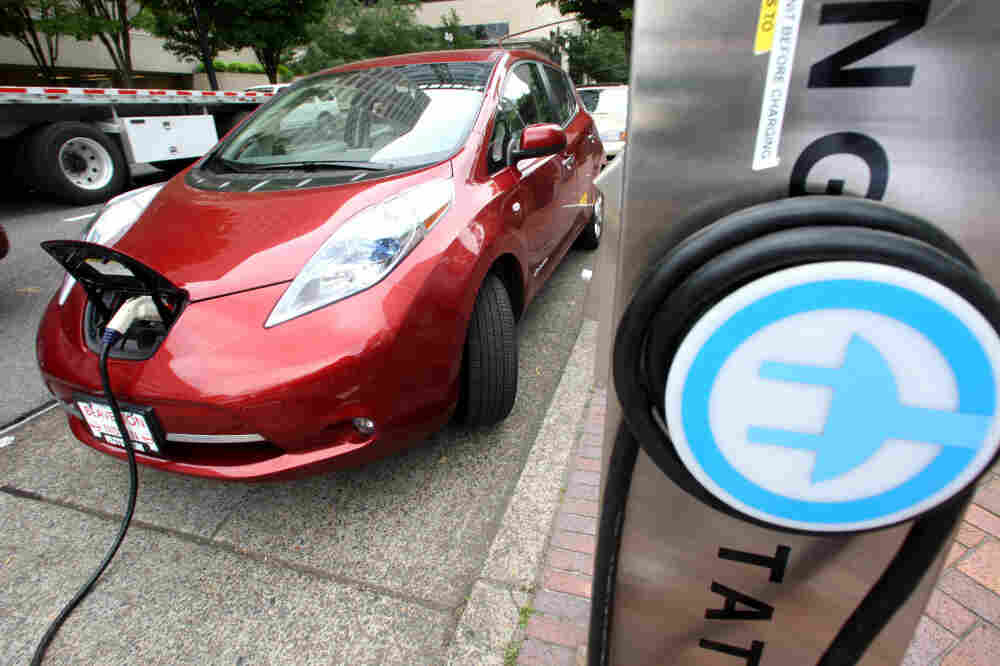 """A Nissan Leaf charges at a station in Portland, Ore., that can recharge an electric car in 30 minutes. Electric cars could be an integral part of meeting 55-mpg fuel standards by 2025, but many consumers are put off by the vehicles' higher price and what some call """"range anxiety."""""""