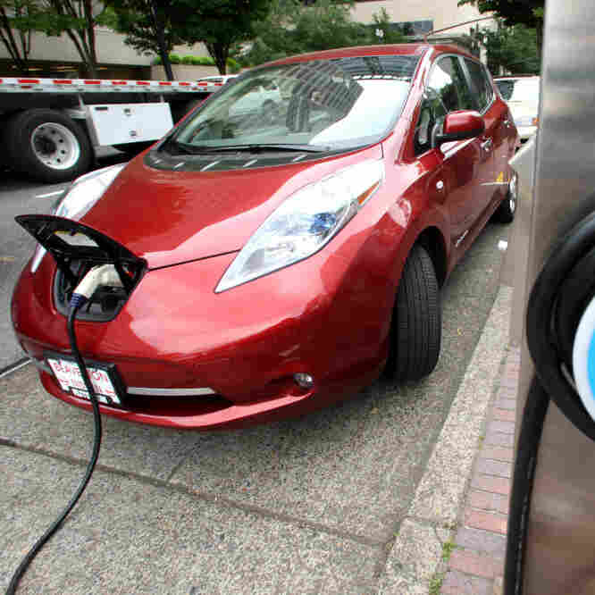 "A Nissan Leaf charges at a station in Portland, Ore., that can recharge an electric car in 30 minutes. Electric cars could be an integral part of meeting 55-mpg fuel standards by 2025, but many consumers are put off by the vehicles' higher price and what some call ""range anxiety."""