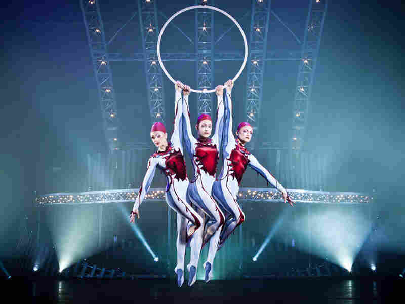 Cirque du Soleil performers hang from aerial hoops in Quidam.