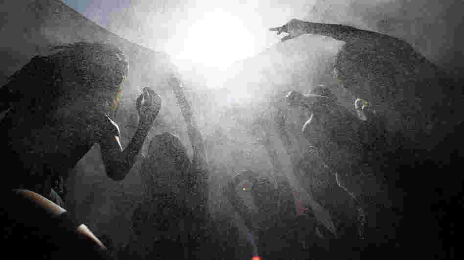 Concertgoers move in a spray of cooling mist as they dance amid the heat of the desert at the hipster Coachella Valley Music & Arts Festival in Indio, Calif., in April.