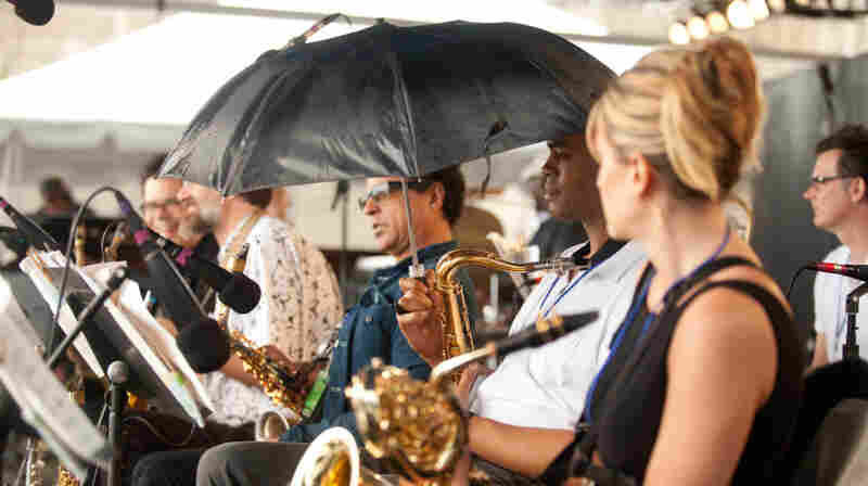 A member of the Mingus Big Band takes shelter from the rain.
