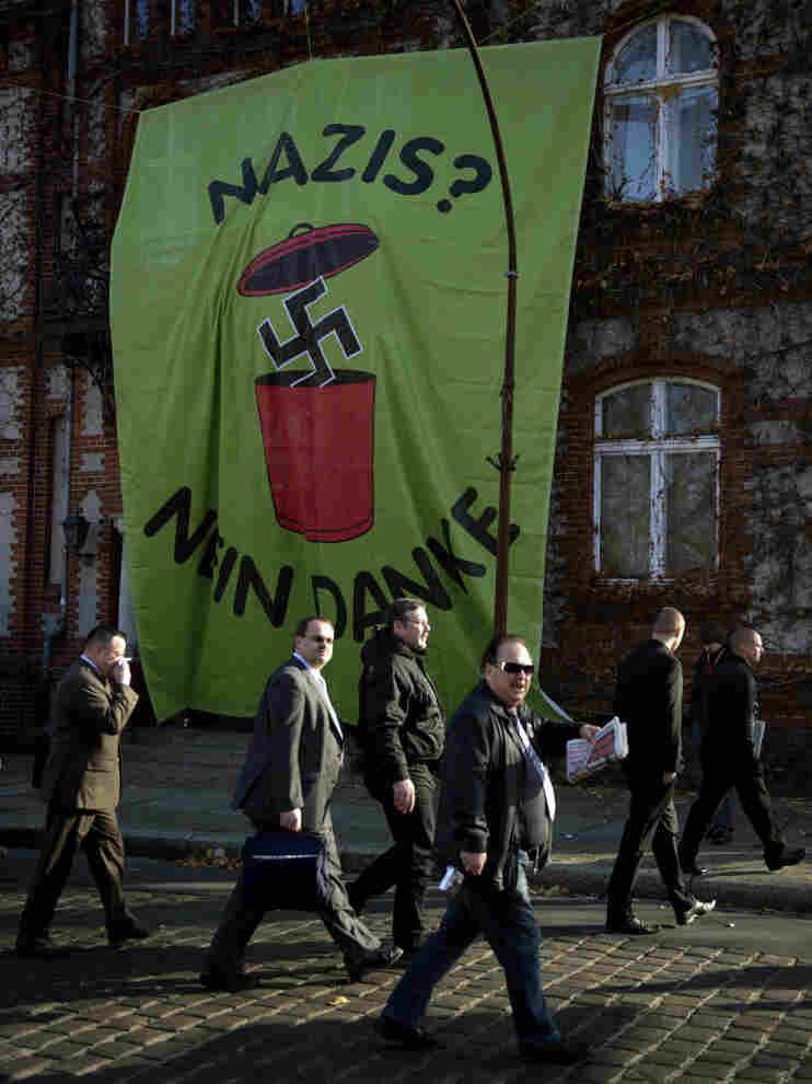 "Supporters of Germany's far-right National Democratic Party walk past a huge banner reading ""Nazis? No, thanks"" as they arrive to attend a party congress on Nov. 12 in Neuruppin, northeastern Germany."
