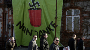 """Supporters of Germany's far-right National Democratic Party walk past a huge banner reading """"Nazis? No, thanks"""" as they arrive to attend a party congress on Nov. 12 in Neuruppin, northeastern Germany."""