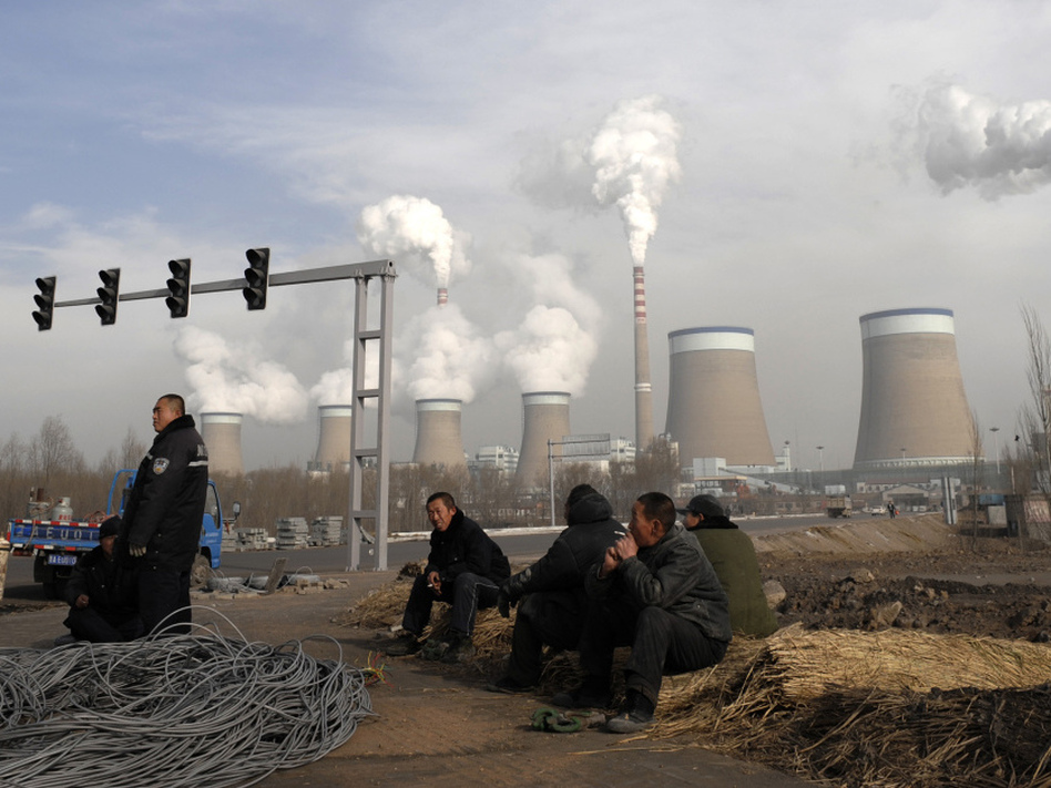 Workers take a break in front of the cooling towers of a coal-fired power plant in Dadong, Shanxi province, China. At a House hearing on Tuesday, Nisha Biswal defended USAID's programs in China, saying the money goes to efforts that include reducing harmful emissions from the country's power plants. (Andy Wong/AP)