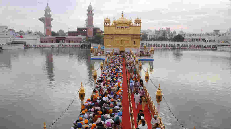 Sikh pilgrims stream into the Golden Temple in Amritsar, India, on Nov. 10. Devout Sikhs from all over India and the world come to Amritsar by the tens of thousands every day — adding to an already sizable carbon footprint. So city and temple officials have joined an environmental group to learn how to incorporate environmentally friendly practices.