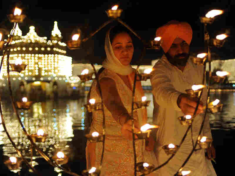 Sikh devotees Puneet Kaur (left) and Gurmeet Singh light lamps as they pay their respects at the Golden Temple in October. Temple authorities are considering installing solar panels for the lighting system to make it more environmentally friendly.