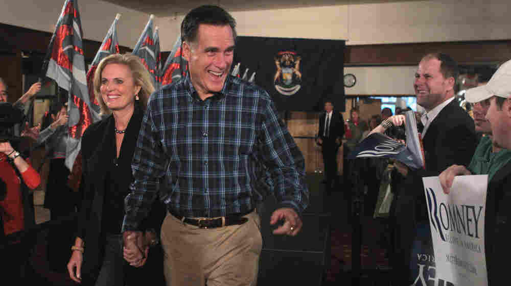 Republican presidential candidate Mitt Romney arrives with his wife, Ann, for a rally at the American Polish Cultural Center earlier this month in Troy, Mich. The former Massachusetts governor is in effect the front-runner in the race for the GOP nomination, despite holding fewer rallies, town hall meetings or media appearances than other candidates.