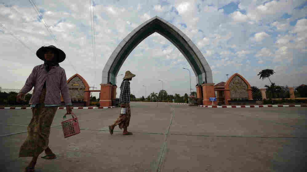 Workers walk past an arch at the entrance to a park in Naypiydaw, the new capital of Myanmar, in January. The then-military rulers of the southeast Asian nation abruptly moved the capital from Yangon to remote Naypiydaw in 2005.