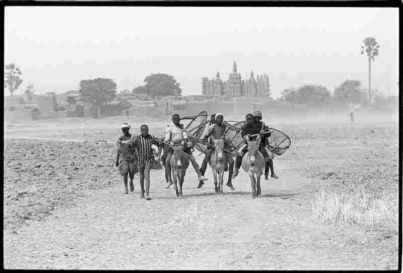 "Djenne, Mali, 1992: In the countryside near Djenne, ""we found these unusual, compact villages surrounded by mud walls, with a mosque towering over the homes. After we left the village these children decided to go fishing in a nearby lake."""