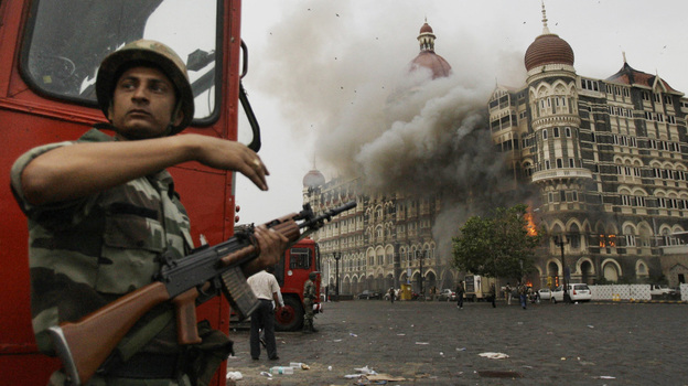 On Nov. 29, 2008, an Indian soldier takes cover as the Taj Mahal hotel burns during a gun battle between Indian military and militants inside the Mumbai hotel.