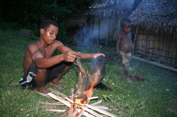 A man prepares an aye-aye, a rare type of lemur found only on the island of Madagascar, for dinner. These primates are an important source of iron and protein despite being critically endangered.