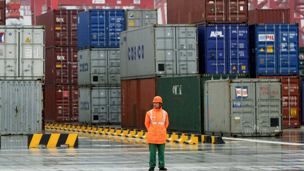 A worker stands in front of containers at the Yangshan deep-water port in 2005 in Shanghai. Republic