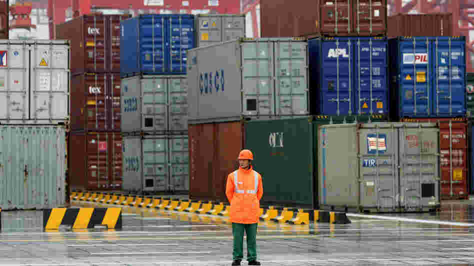 A worker stands in front of containers at the Yangshan deep-water port in 2005 in Shanghai. Republican presidential candidate Mitt Romney has promised to take a hard line against China's trade policies. But he is not the first politician to find in China a convenient campaign foil.