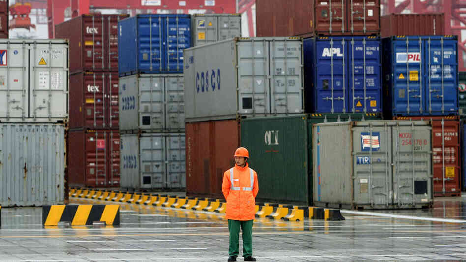A worker stands in front of containers at the Yangshan deep-water port in 2005 in Shanghai. Republican presidential candidate Mitt Romney has promised to take a hard line against China's trade policies. But he is not the first politician to find in China a convenient campaign
