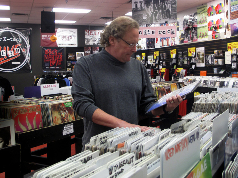 Timmons browses the racks of his now-closed business. The record store will have a final clearance sale on Nov. 29. (Debbie Elliott/NPR)