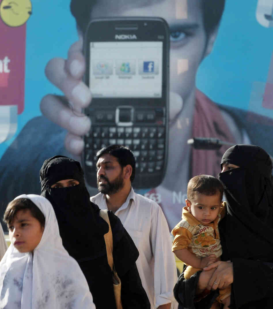 Pakistani families walk past an advertisement for a cellular telephone company in Rawalpindi.