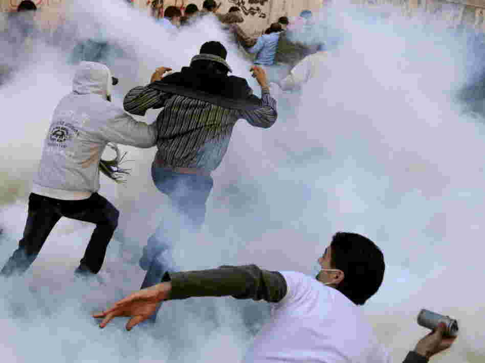 An Egyptian protester prepares to hurl a tear gas canister back at security forces as others run for cover earlier today in Cairo's Tahrir Square.
