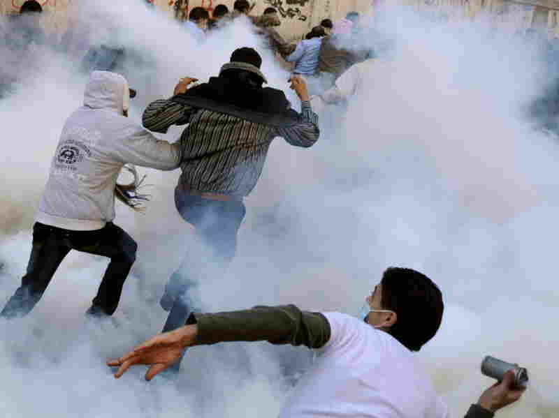 A protester in Tahrir Square prepared to hurl a tear gas canister at Egyptian security forces as others ran for cover.