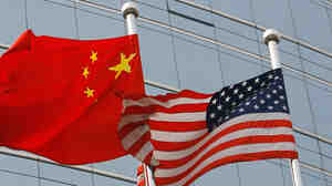 The U.S. and Chinese flags wave outside a commercial building in Beijing.