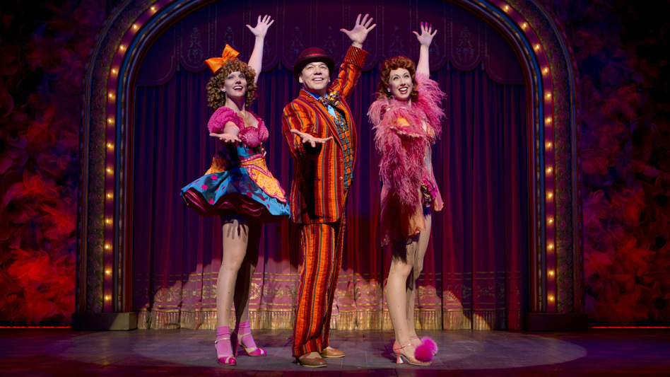 "Danny Burstein, as Buddy Plummer, performs ""Buddy's Blues,"" the high-energy song-and-dance number at the end of Follies, with Jenifer Foote (left) and Kiira Schmidt. (Joan Marcus)"