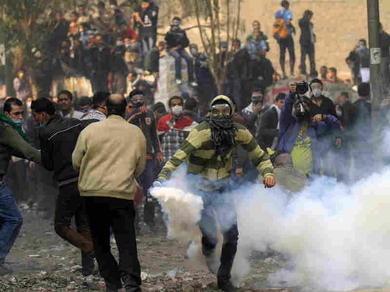 A protester runs to throw a tear gas canister away from the crowd during clashes Tuesday with Egyptian riot police near Tahrir Square.