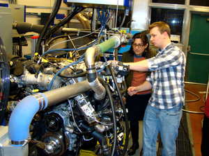 Professor Anna Stefanopoulou (left) examines a V8 internal combustion engine with students Jacob Larimore and Xinfan Lin at the University of Michigan's Automotive Research Center. The researchers model engine performance to improve efficiency.