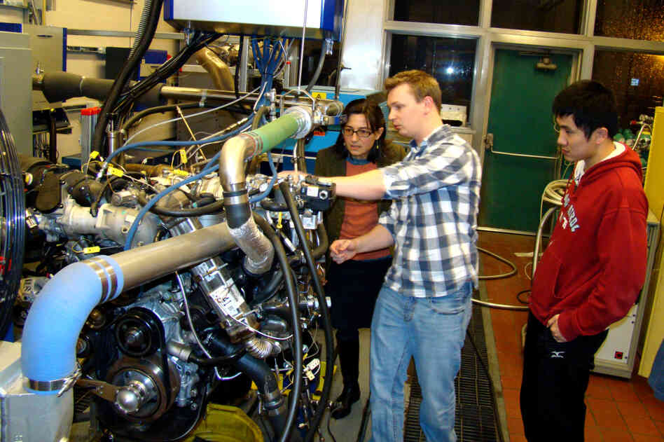 Professor Anna Stefanopoulou (left) examines a V8 internal combustion engine with students Jacob Larimore an