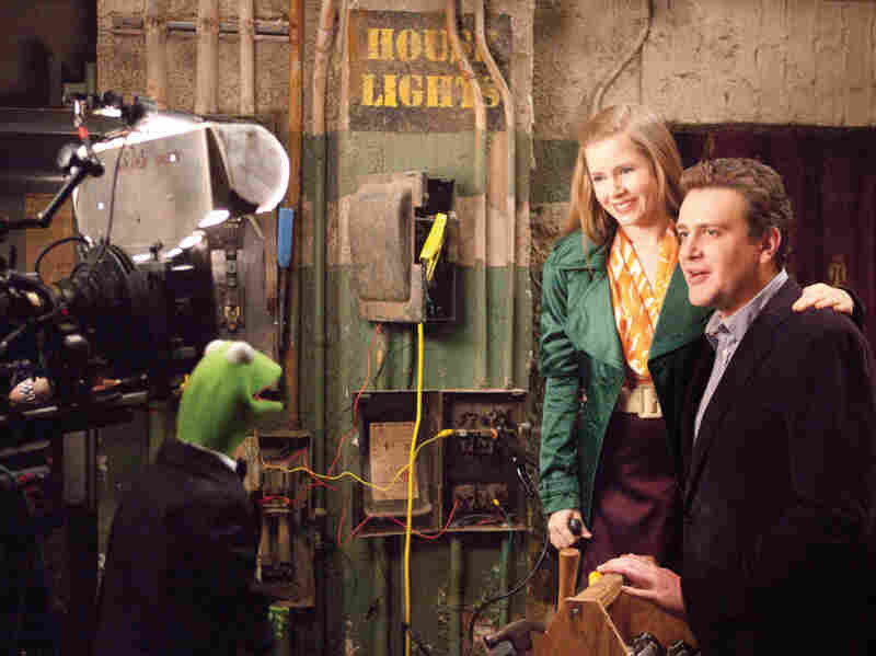 Kermit the Frog does the backstage-chat thing with Amy Adams and Jason Segel in The Muppets.
