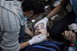 Medics tend to a wounded protester in Tahrir Square. Nearly 2,000 people have been injured in the recent clashes.