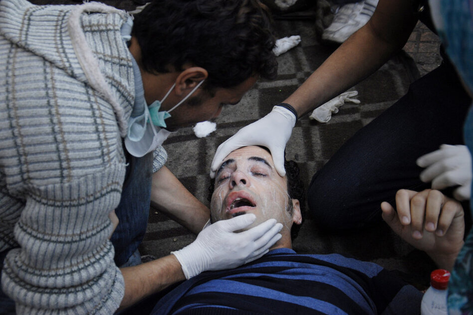 Medics tend to a wounded protester in Tahrir Square. Nearly 2,000 people have been injured in the recent clashes.  (AP)