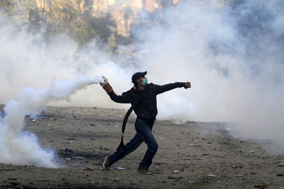 A protester throws a tear gas canister during battles with riot police in Tahrir Square.  (AP)