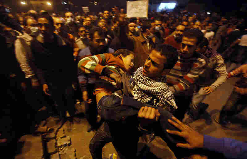 Protesters carry a youth wounded during clashes with police in Tahrir Square.