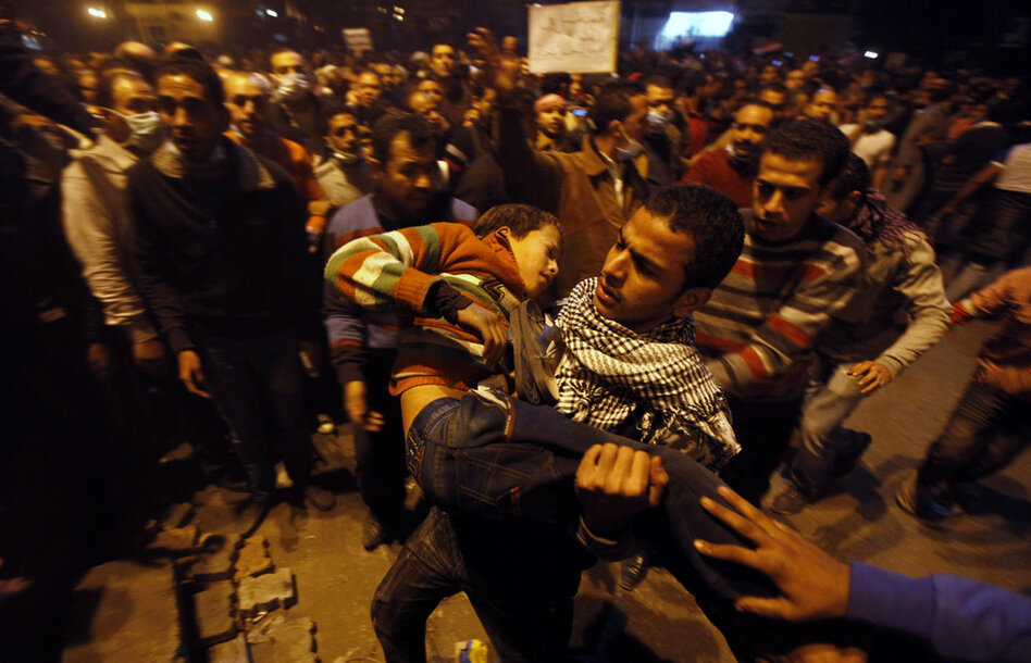 Protesters carry a youth wounded during clashes with police in Tahrir Square.  (AP)