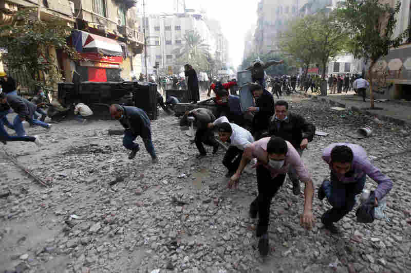 Protesters run for cover during clashes with Egyptian riot police Tuesday near Tahrir Square in Cairo.
