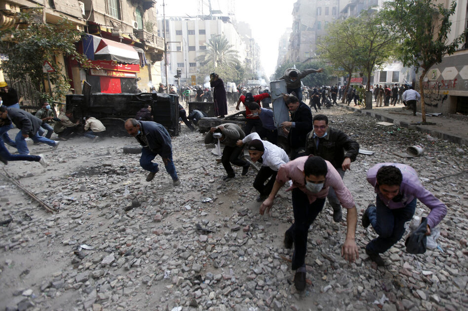 Protesters run for cover during clashes with Egyptian riot police Tuesday near Tahrir Square in Cairo.  (AP)