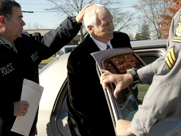 "Gerald ""Jerry"" Sandusky, center, is placed in a police car in Bellefonte, Pa. on Saturday, Nov. 5."