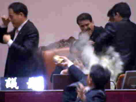 This still image taken from video shows lawmaker Kim Sun-Dong (bottom) of the Democratic Labor Party detonating a tear gas canister and throwing it toward the chairman's seat at the National Assembly.